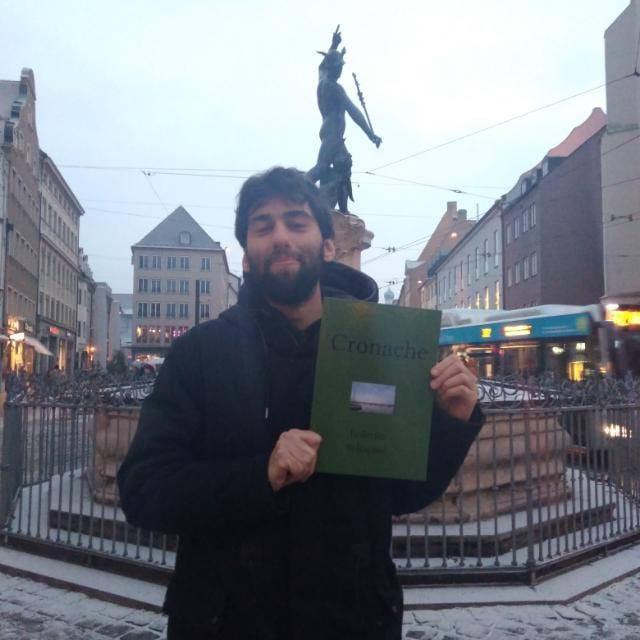 """L'autore Federico immortalato in una nota piazza di Augsburg mentre tiene in mano una copia del famoso libro """"cronache"""""""